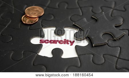 Word scarcity under jigsaw puzzle piece with coins on the side