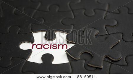 Word racism under black jigsaw puzzle piece