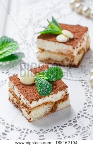 Mini cakes tiramisu with white chocolate cocoa and candies on light background close up. Delicious dessert and candy bar.
