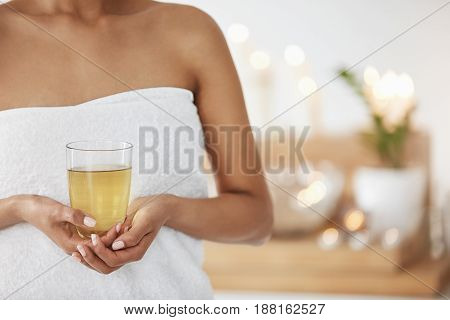 Close up photo of young girl in towel holding glass with green tea in spa salon.