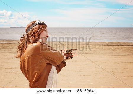 Beautiful Young Girl With A Toy Airplane On The Shore Of The Bay In The Clothes Of The Pilot, Copy S