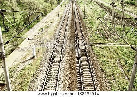 Empty railway tracks in a rural scene with grass and electric lines