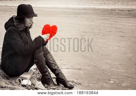 A Young Woman In A Hat And Coat Sits On The Shore Of The Bay On A Fishing Net With A Plush Heart In
