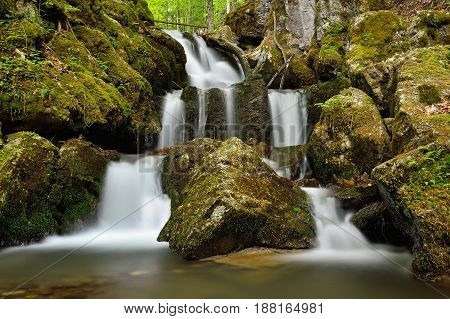 Spring landscape with huge water falling detail. Colossal cascade Tajovsky waterfall in Slovakia.