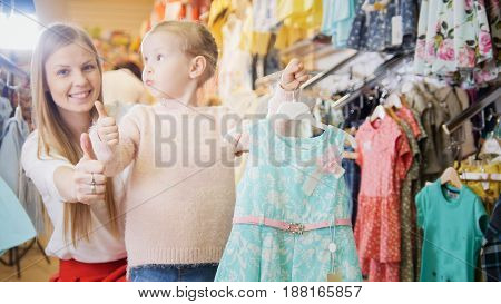 Shopping for kids - mother and daughter noted that blue dress is cool.