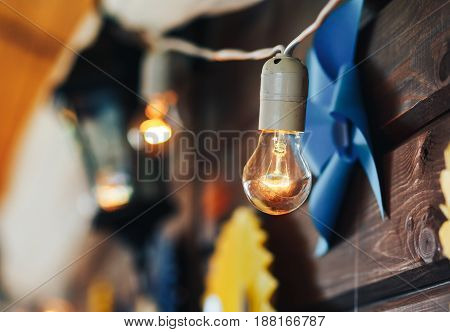 Incandescent lamps on a wooden wall decoration of the room