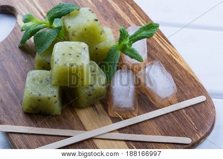 Homemade natural popsicles made with fresh kiwi with mint leaves. Summer Ice Cream, fruit dessert