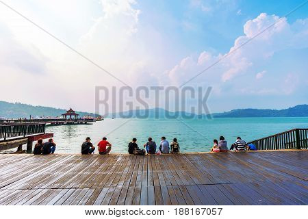 NANTOU TAIWAN - MAY 06: Tourists sitting and relaxing on stairs watching the scenic view of Sun Moon Lake on May 06 2017 in Nantou