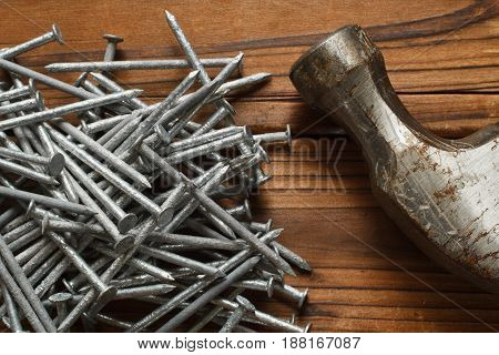 Galvanized carpentry nails and hammer on wood.