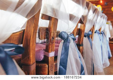 Close-up of wooden chairs with blue bows