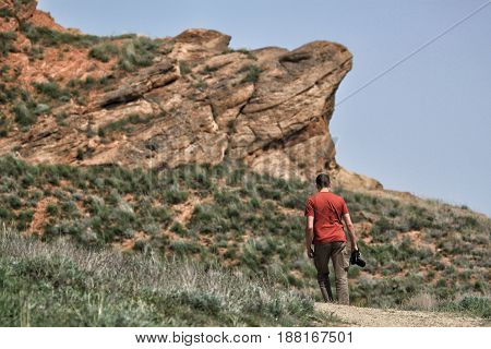 Man with camera in hand walking to the mountain