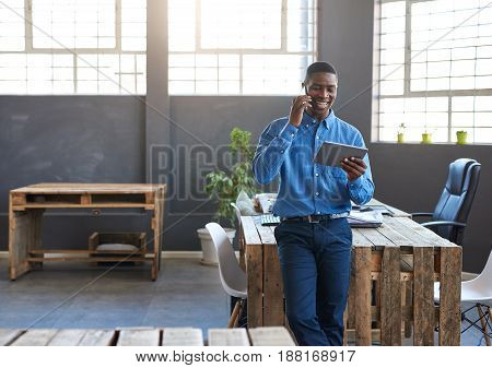 Smiling young African businessman leaning on his desk in a large modern office talking on a cellphone and working on a digital tablet