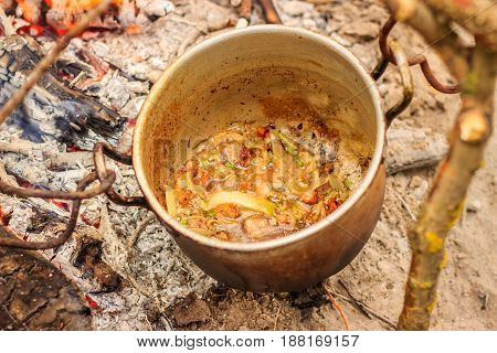 Eating in a pot in the nature is made roast with onions and bacon for the preparation of millet porridge looks appetizing and very tasty