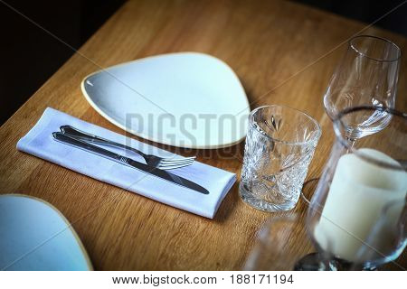 Close up shot of a fork and knife on a wooden table on a napkin near an empty plate.