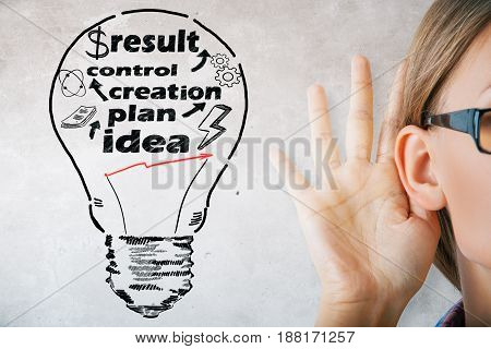 Young woman listening carefully on concrete background with drawn lamp and text. Idea concept