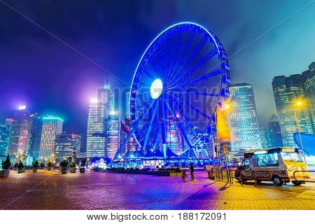 HONG KONG CHINA - APRIL 25: This is a night view of the Hong Kong observation wheel a popular tourist attraction with financial district architecture in the background on April 25 2017 in Hong Kong