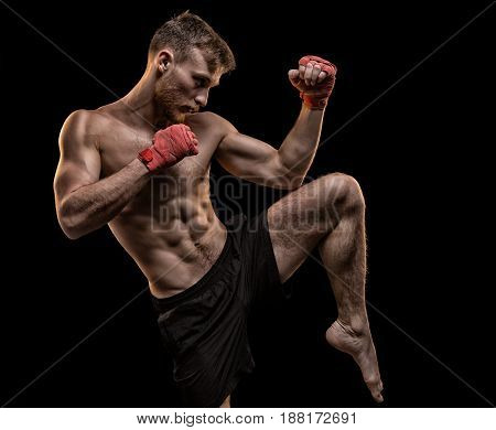 Bearded fighter during workout on black background