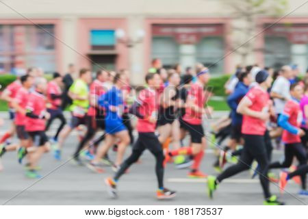 Large group of running athletes on the street, city marathon, blur effect, unrecognizable faces. Sport, fitness and healthy lifestyle concept. For modern backdrop