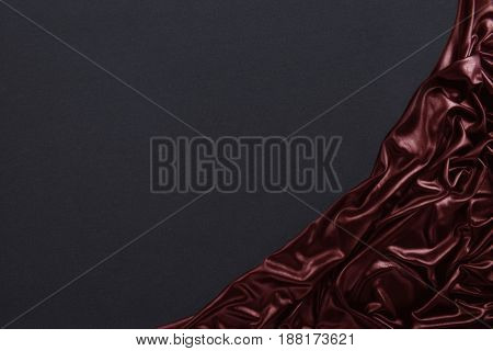 Dark stone background with red silk clothes in right corner.