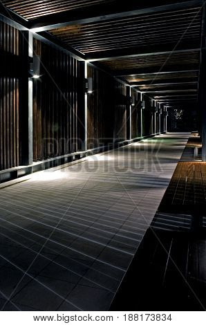 Wooden tunnel with spot lights in an outdoor park at night.