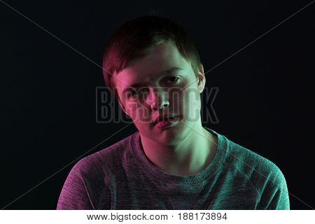 Portrait of passive teenager guy on black background