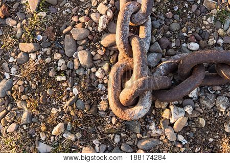 DUESSELDORF, GERMANY - JANUARY 20, 2017: Details of an old anchor chain on the ground are nicely enlighted by the evening sunlight.