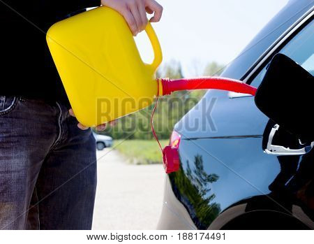 Man pouring fuel into the gas tank of his car from a canister.