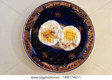 Two Halves Of Boiled Egg With Sauce And Pepper