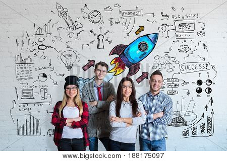 Cheerful european team on brick background with business sketch. Start up concept