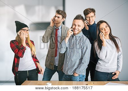 Attractive cheerful european team members talking on the phone in office. Communiction concept