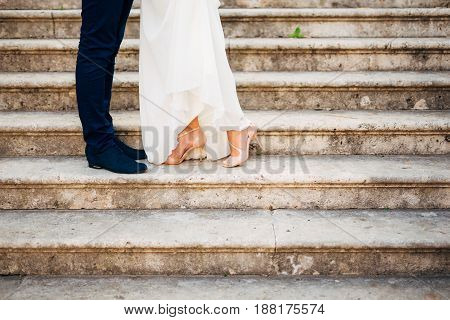 Love and happiness on wedding day. Closeup of bride's and groom's feet and shoes and wooden decoration 'love' in their hands.