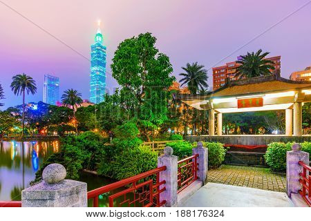 TAIPEI TAIWAN - APRIL 20: This is a view of a traditonal style pavilion with the Taipei 101 building in the background at night in Zhongshan park on April 20 2017 in Taipei