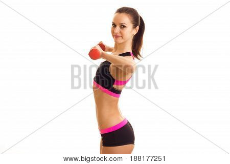 young slender sport girl stands sideways and holding a dumbbell is isolated on a white background