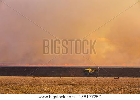 An ATV parked on the edge of a burning agriculture field with a wall of smoke in the background