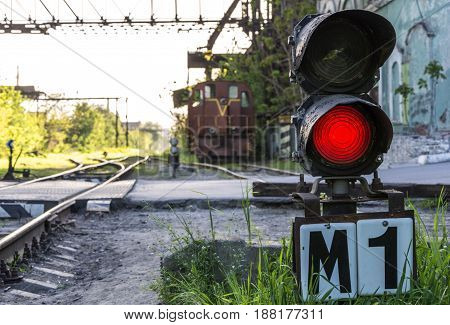 Semaphore shines a red light on the background of the locomotive