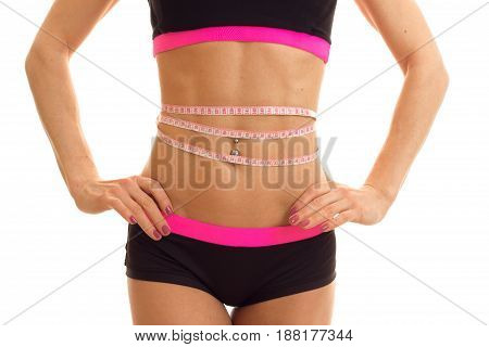 beautiful bouncy tummy with the press of a young girl with a measuring tape on waist close-up isolated on white background