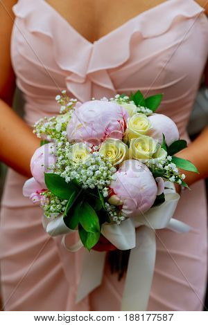 Young Caucasian Woman In Pink Lace Dress Holds A Bouquet