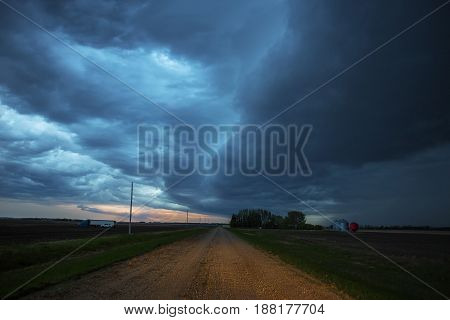 Ominous thunder storm clouds over a agricultual prairie landscape at night