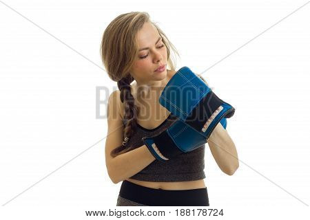 young gorgeous blonde stands with pigtail and stares at his hands in boxing gloves close-up isolated on white background