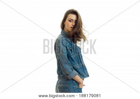 young cute brunette with beautiful hair stands sideways in a jeans suit and looking at camera isolated on white background