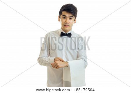 charming young waiter stands upright with cloth on hand isolated on white background