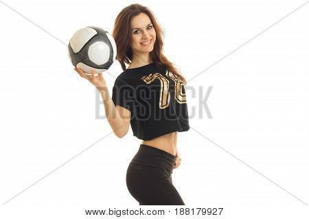 a charming young athletic girl stands sideways smiles and raised the ball in hand isolated on white background