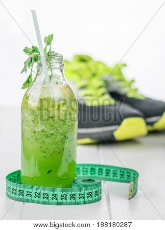 Bottle cucumber smoothie with kiwi and parsley. Running shoes in the background. The concept of sports diet food for weight control.