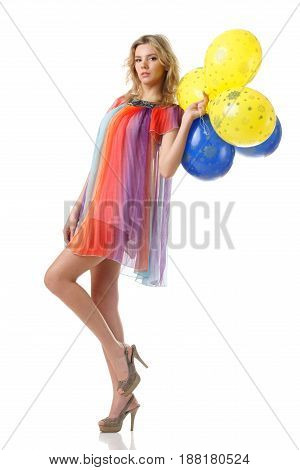 young pretty female in colourful dress with yellow and blue balloons