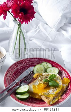 Breakfast in bed.Traditional breakfast of fried eggs with coffee bagel and oatmeal in bowl on wood serving tray on unmade bed