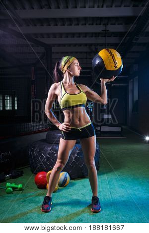 A strong girl in a gym in dark colors trains with the ball. Health, sport concept