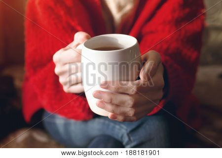 Closeup of female hands with a cup of beverage. Beautiful girl in red sweater holding cup of tea in the morning sun.
