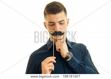 otherwise Winsome young guy keeps near the face, paper mustache isolated on white background