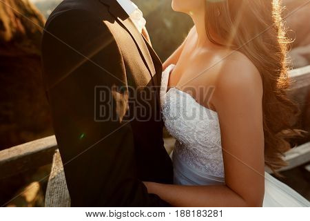 Gorgeous Wedding Couple Embracing In Sunlight. Happy Stylish Bride And Groom Holding Hands In Evenin