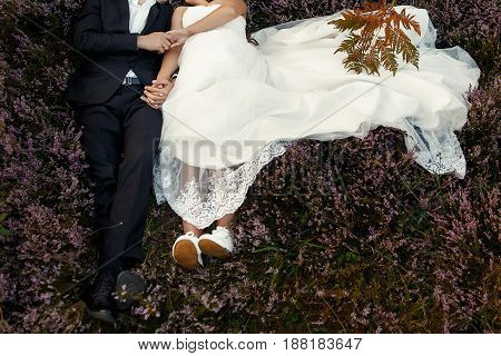 Happy Stylish Bride And Groom Embracing In Sun Light Lying In Heather Mountains. Gorgeous Wedding Co